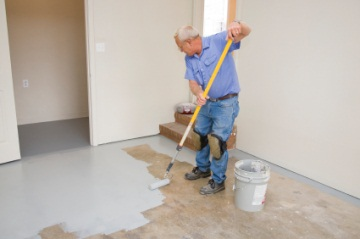 Painter applying epoxy paint to garage floor.